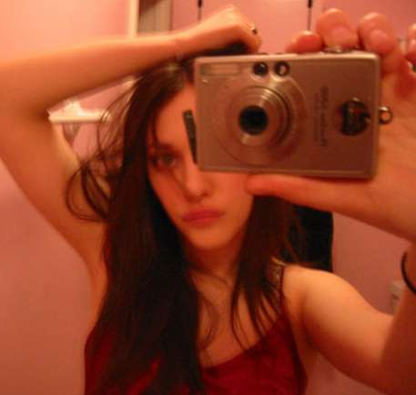celebrity kat dennings taking a photo of herself with a normal camera