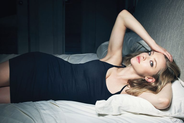 famous amanda seyfried laying in bed with tight black dress on looking sexy
