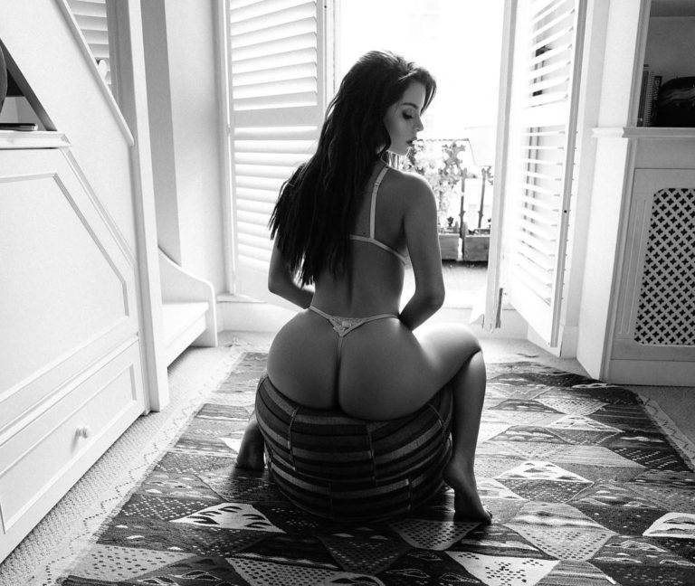 Black and white photo of Demi Rose's ass in a white thong