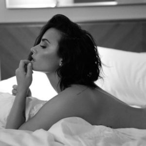 Demi Lovato black and white pic of nude photo shoot laying on bed
