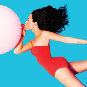 Demi Lovato blowing a pink balloon in the air