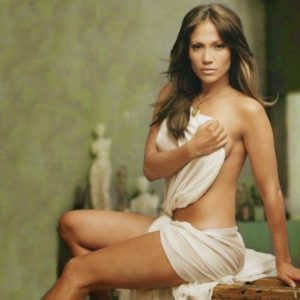 Jennifer Lopez with her top off sitting on a table