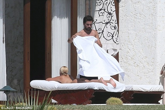 Scott Disick covering up Sofia Richie with a towel